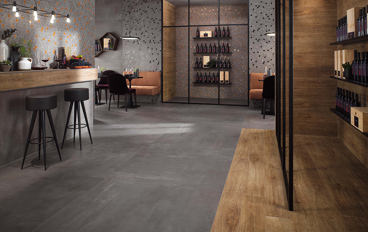 Modern style restaurant interior design with concrete and wood effect large format porcelain tiles - Boost Smoke 120x120 and Arbor Cognac Matt 18,5x150.