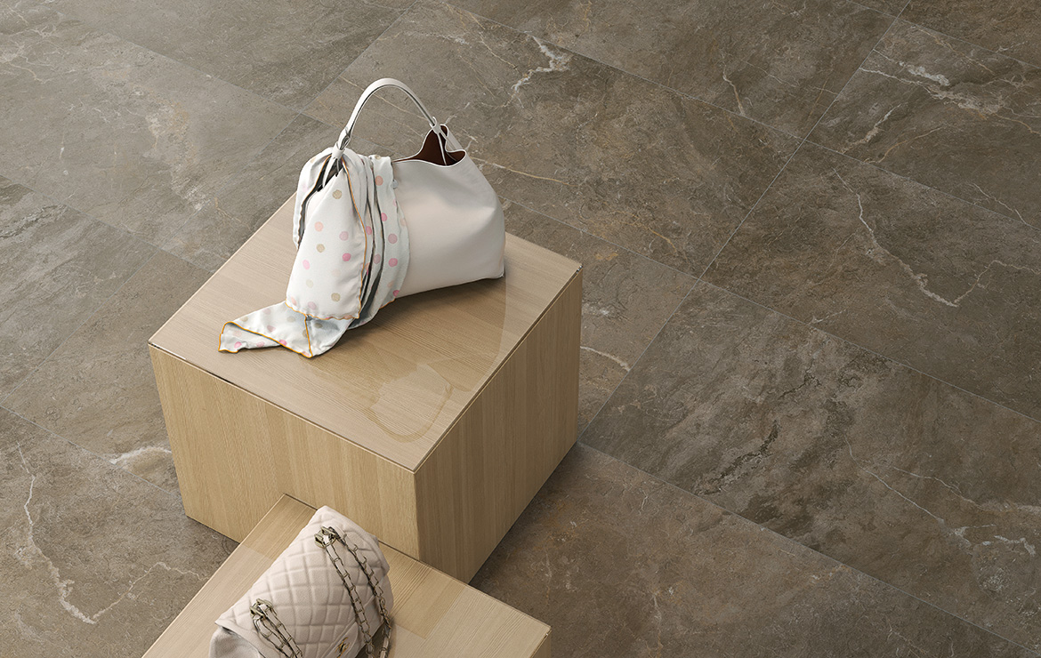 Clothing shop floor design with the large format natural stone effect porcelain tiles - Cave Noce 45x90.