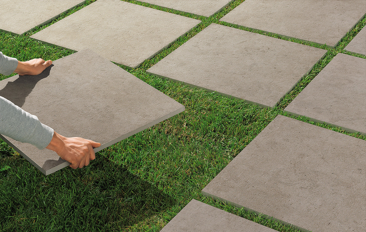 Exterior paving tiles dry installation directly on the grass.